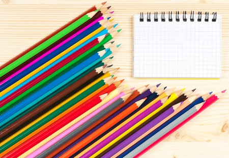 sharpened: Bright colorful pencils with notebook over wooden surface