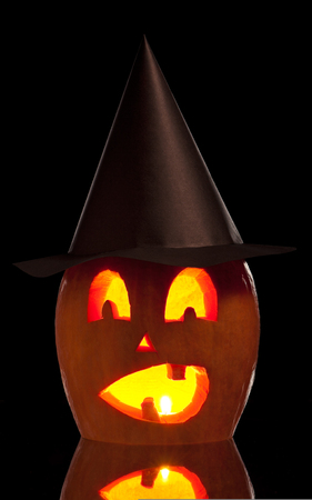 hollows: Terrible halloween pumpkin with candle over black background