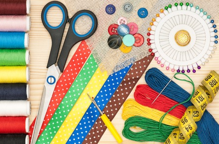 Colorful threads with sewing accessories over wooden surface