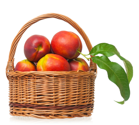 Ripe nectarines in the wicker basket isolated on a white background