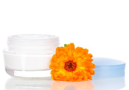 Jar of moisturizing face cream and fresh marigold flower isolated on white background