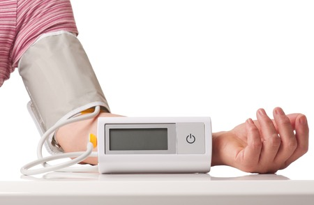 Female hand with electronic pressure measuring instrument over white background Stock Photo