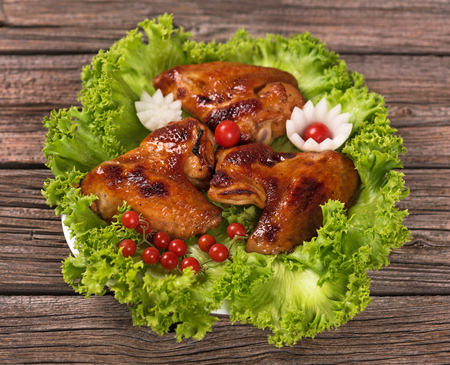 Baked chicken wings with fresh vegetables over old wooden background