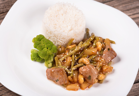 Tasty beef Stroganoff with rice and vegetables over old wooden surface