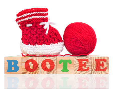 Bright cute little bootee with playing cubes isolated over white background Reklamní fotografie
