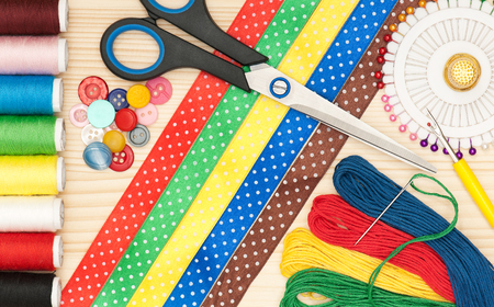 Spirale: Bright sewing accessories over wooden surface close-up