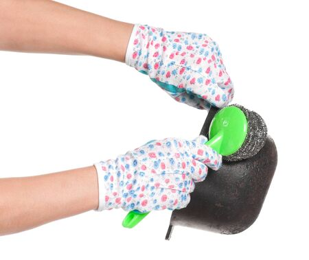 Hands in gloves hold a cauldron and wire wool scourer isolated on white background