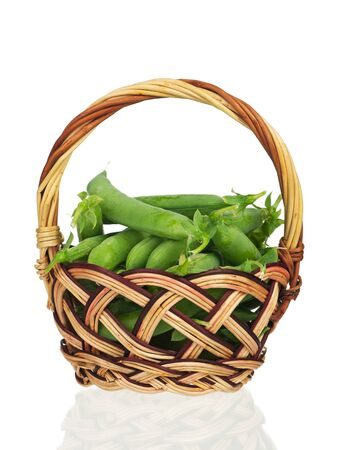 Fresh peas pods in a wicker basket isolated over white background