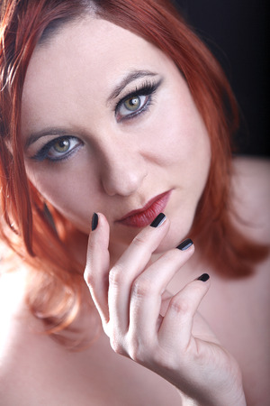 red head woman: Red head woman with black nails looking into the camera