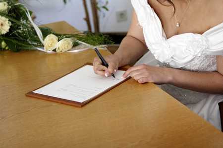 Bride signs the marriage contract photo
