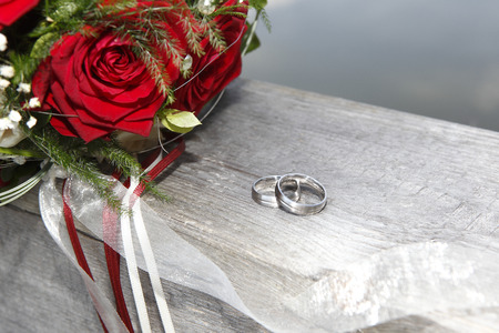 Red rose bouquet with wedding rings photo