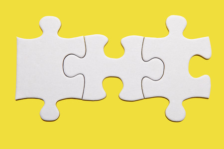 Three white puzzle pieces on yellow background Stock Photo