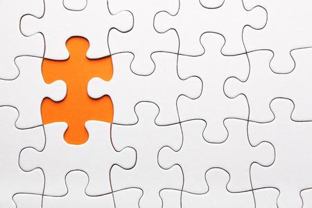 White puzzle piece missing on orange background 写真素材