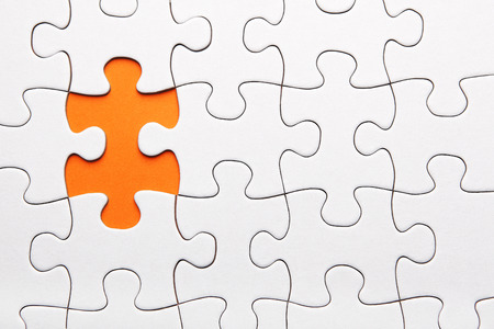 White puzzle piece missing on orange background Stock Photo