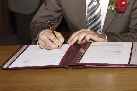 Groom signs the marriage contract Stock Photo - 27918029