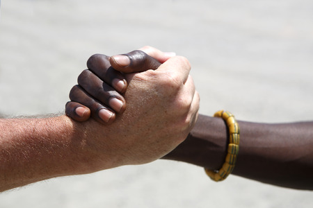 Handshake between a Caucasian and an African on gray background