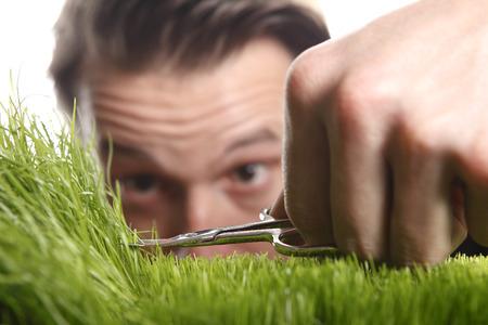 Jonge man snijdt Engels gazon met een nagelschaartje Stockfoto