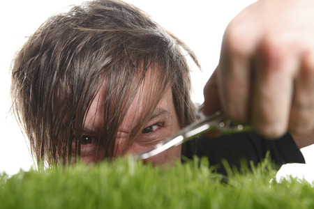 nail scissors: Young man cuts English lawn with a nail scissors