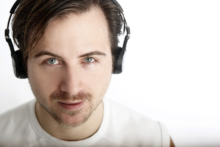 Attractive man with headphones looks into the camera photo