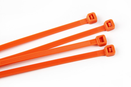 dimensionally: Cable ties in orange in front of white background