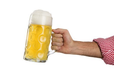 Man in traditional Bavarian shirt holds mug of beer in front of a white background photo