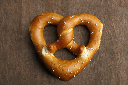 Traditional bavarian pretzel formed as a heart on a brown background photo