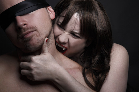 Female vampire with red lips bites man in the neck photo