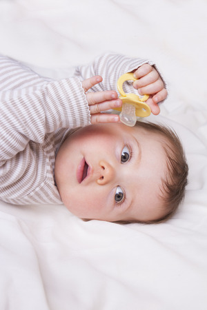 lies down: Baby girl with dummy lies down on a white blanket Stock Photo