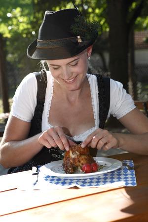 slaughtering: Ragazza bionda mangia mezzo pollo in una tradizionale birreria bavarese Archivio Fotografico