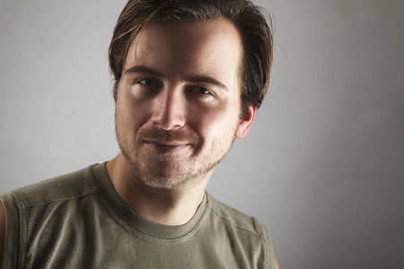get a workout: Portrait of an attractive man with green shirt in front of gray background