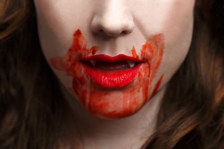 coagulate: Female vampire with bloody moutgh after biting someone