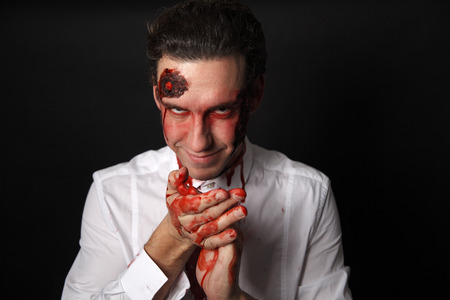 corpses: Psychopath with bloody hands in a white shirt Stock Photo
