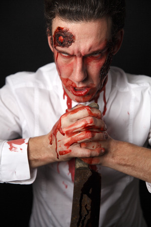 Psychopath with bloody knive in a white shirt photo