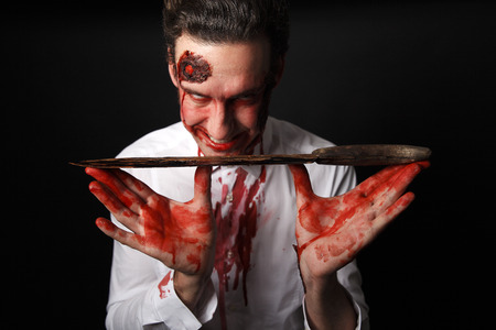 corpses: Psychopath with bloody knive in a white shirt