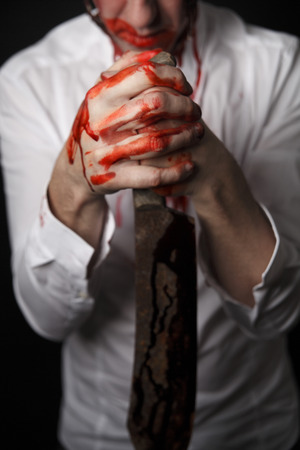 carnage: Psychopath with bloody knive in a white shirt