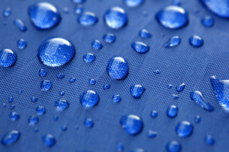 Closeup of rain drops on a blue umbrella