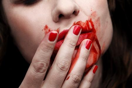 coagulate: Female vampire licking blood off of her fingers
