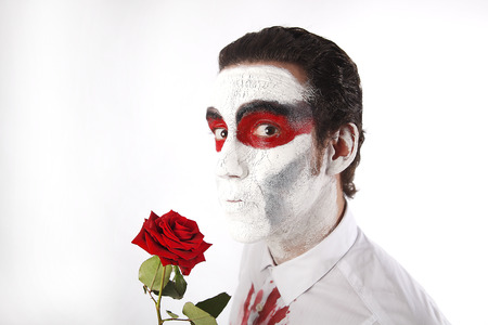panicky: Man with white mascara and bloody shirt holds red rose in front of a white background