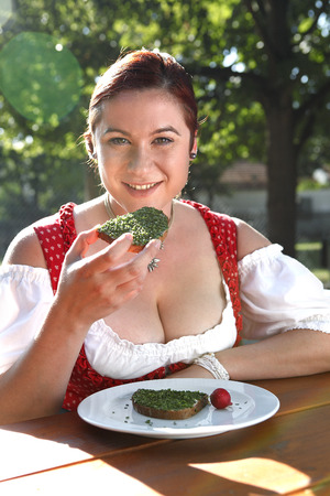 red head woman: Red head woman in typical Bavarian costume eats bread with chives in a Bavarian beer garden
