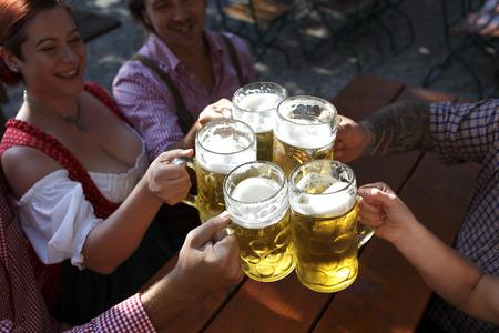 People in traditional costumes drinking beer in a Bavarian beer garden 写真素材