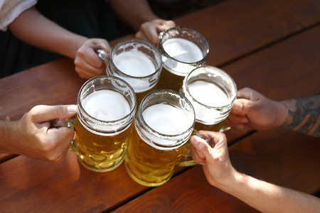 People in traditional costumes drinking beer in a Bavarian beer garden Foto de archivo