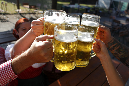 People in traditional costumes drinking beer in a Bavarian beer garden Stockfoto