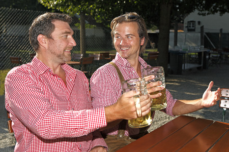 drinks after work: Two Bavarians sitting in a beer garden and drink smb.?s health