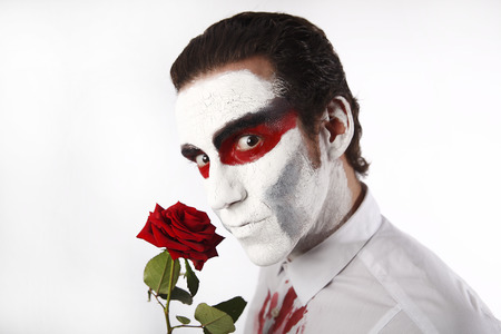 Man with white mascara and bloody shirt holds red rose in front of a white background
