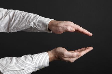 decreasing in size: Mani maschili proteggono qualcosa di fronte a uno sfondo nero Archivio Fotografico