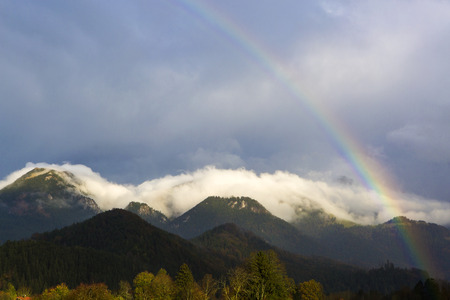 Landscape of Bavarian mountains with rainbow and fog photo