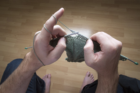 Closeup of a man knitting a green scarf at home
