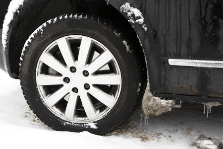 winter tires: Closeup of frozen ice on car tires in winter