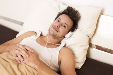 undershirt: Smart guy in white undershirt lies in bed and listens to music Stock Photo