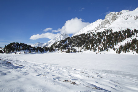 Frozen lake Obersee in the Austrian Alps between snowy mountain landscape photo